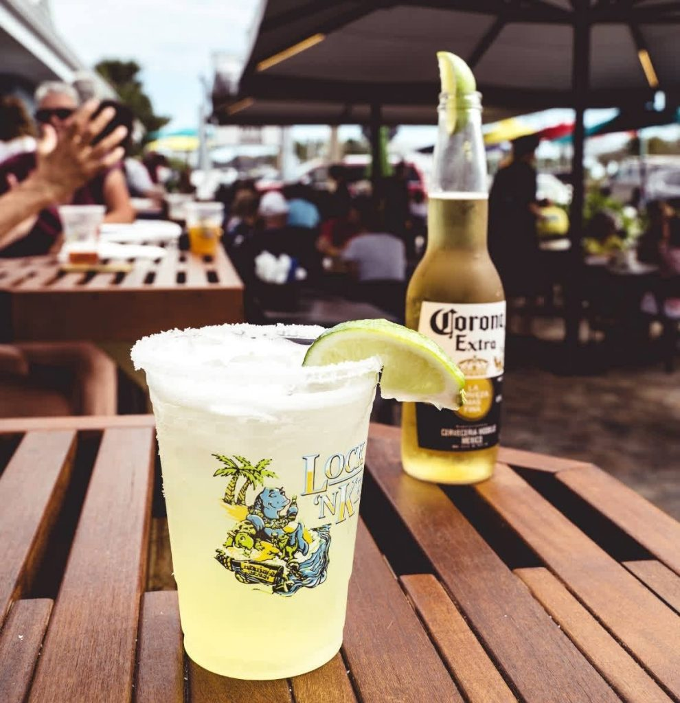 Corona beer bottle with a lime behind a margarita in a Lock N Key cup