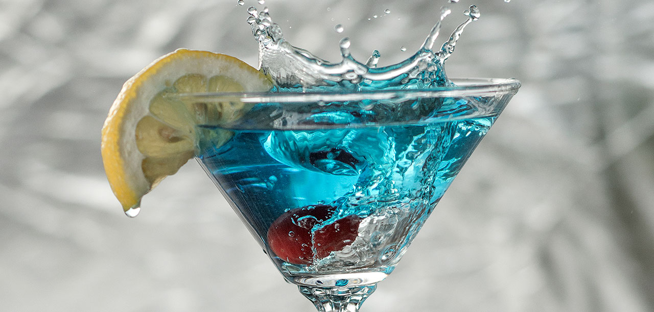 Cherry splashing into blue Martini