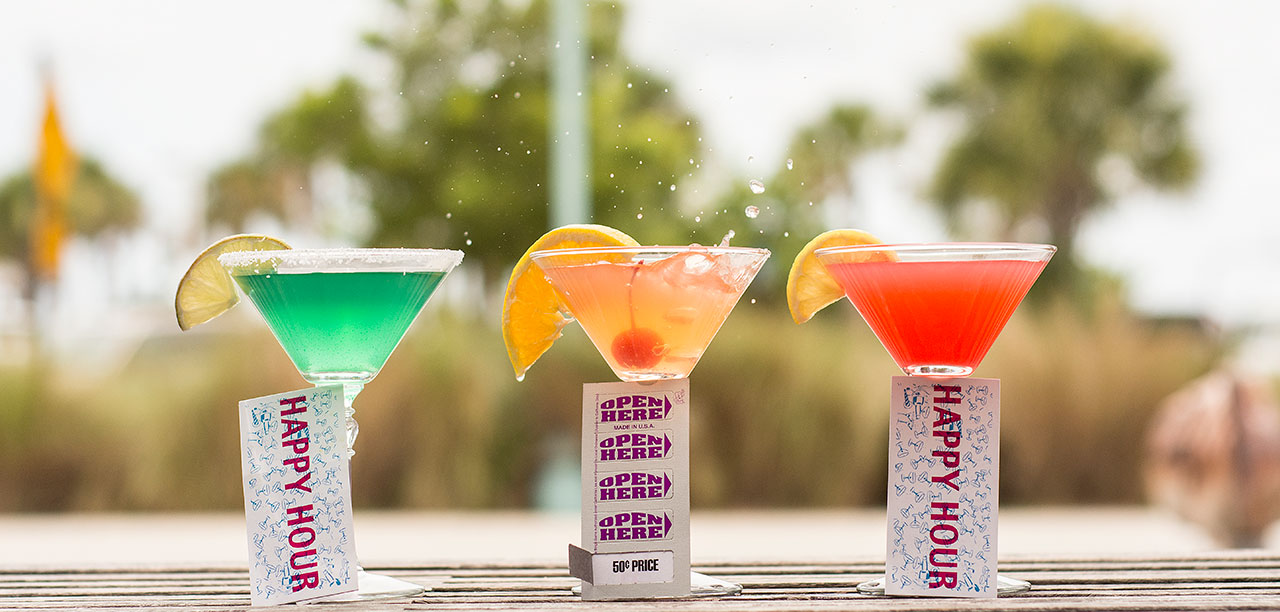 three colorful drinks with happy hour tickets