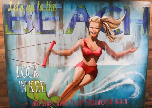 Sign with surfing woman and writing: Let's go to the Beach - Lock 'N Key - Just Steps Away From Englewood Beach